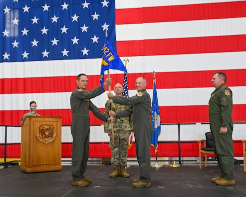 A man hands a blue guidon to a slightly shorter man in front of an enormous American flag while two other men watch and a woman stands behind a podium.