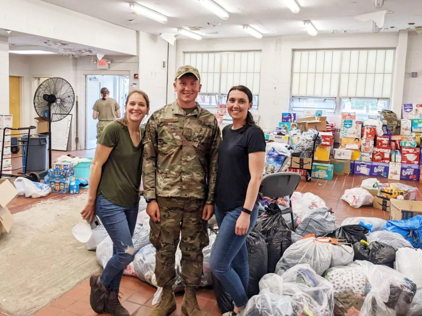 From left to right: Senior Airman Katlyn Legerstee, Staff Sgt. Jake Leonard, and Tech. Sgt. Cassandra Dowling, of the 157th Air Refueling Wing, inside the donation center at Joint Base McGuire-Dix-Lakehurst, Sept. 17, 2021.