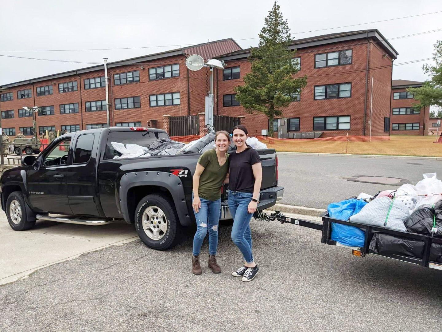 Senior Airman Katlyn Legerstee, left, and Tech. Sgt. Cassandra Dowling, right, both of the 157th Air Refueling Wing, stand in front of the pickup truck and trailer they loaded with clothing donated for vulnerable Afghans temporarily living at Joint Base McGuire-Dix-Lakehurst, Sept. 17, 2021.