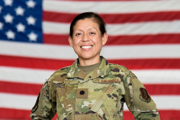 Lieutenant Colonel Daisy Ortiz poses in front of an American Flag in the security forces hangar on Joint Base McGuire-Dix-Lakehurst, October 2, 2021.