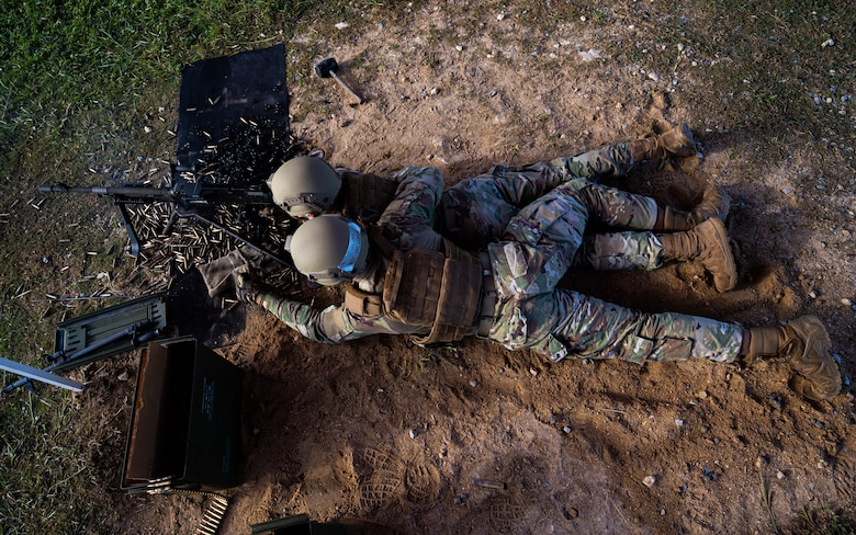 Airman 1st Class Lance Lee, left, 18th Security Forces Squadron armorer, and Airman 1st Class Malaka Bewar, right, 18th SFS armorer, fire an M240B machine gun at Camp Hansen, Japan, Sept. 30, 2021. Heavy machine gun teams fire in two-man teams with the assistant gunner providing assisted stabilization, reloading and barrel changes for the primary gunner. (U.S. Air Force photo by Airman 1st Class Stephen Pulter)
