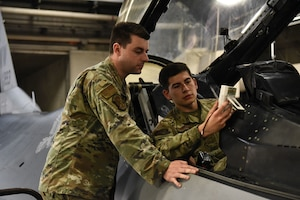Two airmen hold an oxygen purity tester connected to an F-16 Fighting Falcon.
