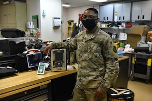 A military member stands next to a oxygen purity tester in his office