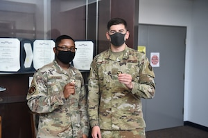 Two military members stand side by side displaying the coins they were awarded by the base commander