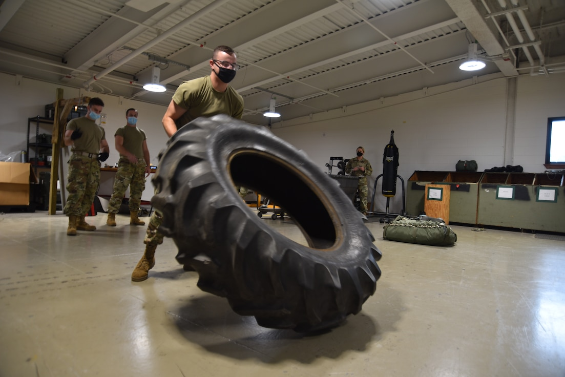 """Staff Sgt. Nicholas Willig, 41st Aerial Port Squadron air transportation craftsman, participates in the """"fit to fight"""" portion of the Port Dawg Challenge at Keesler Air Force Base, Miss., Oct. 2, 2021. This part of the fitness portion has Willig raising a heavy tire tread up to pitch it over multiple times as his teammates and evaluators observe. (U.S. Air Force photo by Tech. Sgt. Michael Farrar)"""