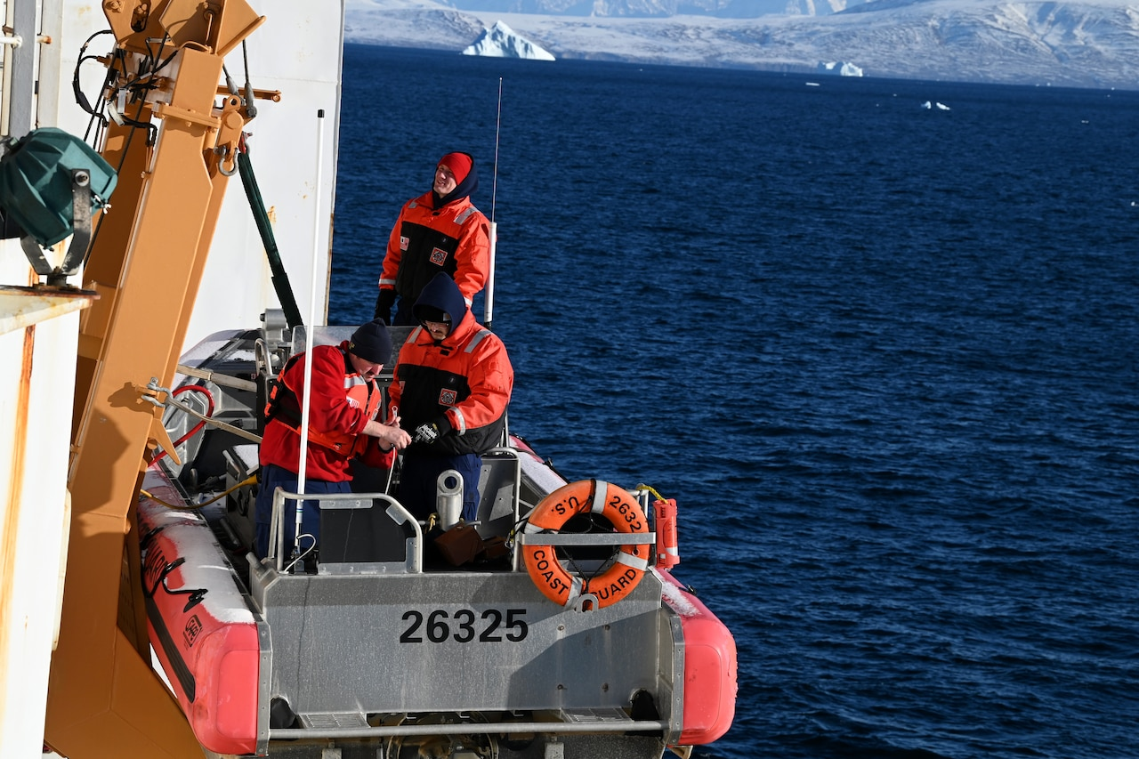 Coast Guardsmen stand in a small boat above the ocean.