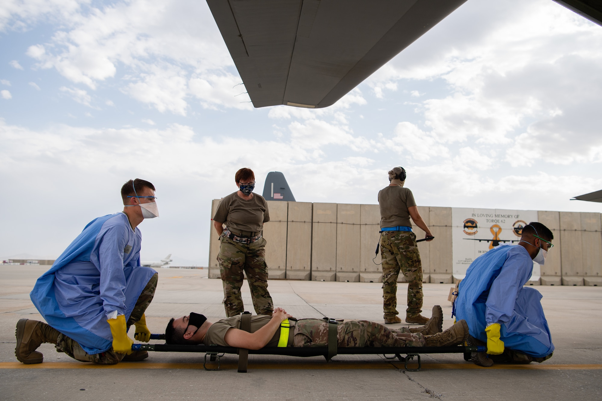 U.S. Air Force members assigned to the 405th Expeditionary Aeromedical Evacuation Squadron lift a litter for transport during a training exercise for the Negatively Pressurized Conex-Lite in Southwest Asia, July 30, 2020.  The NPC-Lite is the latest isolated containment chamber developed for intra-theater airlift of individuals with infectious diseases like COVID-19 and is designed to fit inside a C-130 aircraft.  (U.S. Air Force photo by Staff Sgt. Justin Parsons)