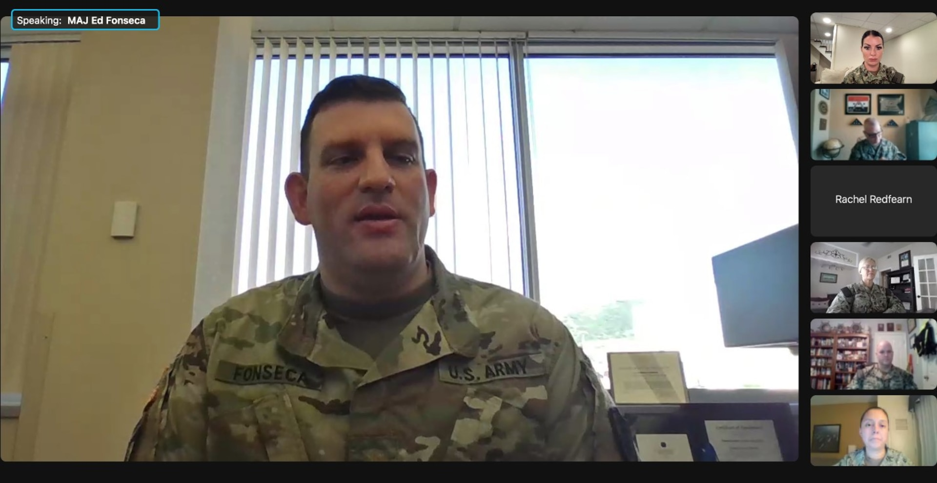A group of male and female service members on their computers talking to each other