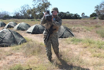 a Civil Engineer Corps (CEC) Officers School Basic Qualification Course student, transfers a grenade launcher from the combat operations center to the defense in-depth training area