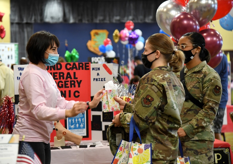 U.S. Air Force Senior Airman Elizabeth Davidson, 81st Surgical Operations Squadron medical technician, provides informative gifts to Staff Sgt. Brandy Michaud, 81st Medical Support Squadron information systems NCO in charge, and Staff Sgt. Yesenia Fewson, 81st MDSS cyber security NCO in charge, during the 10th Annual 81st Medical Group Health Expo inside the Bay Breeze Event Center at Keesler Air Force Base, Mississippi, October 1, 2021. The 81st MDG hosted the walk-in event which included information booths and scheduling appointments for multiple types of cancer and chronic diseases in honor of Breast Cancer Awareness Month. (U.S. Air Force photo by Kemberly Groue)