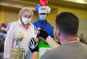 U.S. Air Force Staff Sgt. Travis Brown, 81st Surgical Operations Squadron orthopedic technician, passes on hand anatomy information to Retired Master Sgt. Joe Lee and his wife, Vi, during the 10th Annual 81st Medical Group Health Expo inside the Bay Breeze Event Center at Keesler Air Force Base, Mississippi, October 1, 2021. The 81st MDG hosted the walk-in event which included information booths and scheduling appointments for multiple types of cancer and chronic diseases in honor of Breast Cancer Awareness Month. (U.S. Air Force photo by Kemberly Groue)