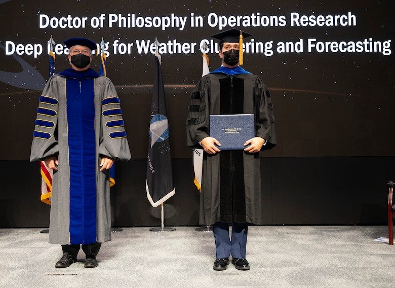 During a graduation ceremony on Sept. 16, 2021, Dr. Walter Jones, director and chancellor of the Air Force Institute of Technology, stands with Capt. Nathanael Beveridge as he receives his Doctor of Philosophy diploma in operations research. (U.S. Air Force photo by R.J. Oriez)