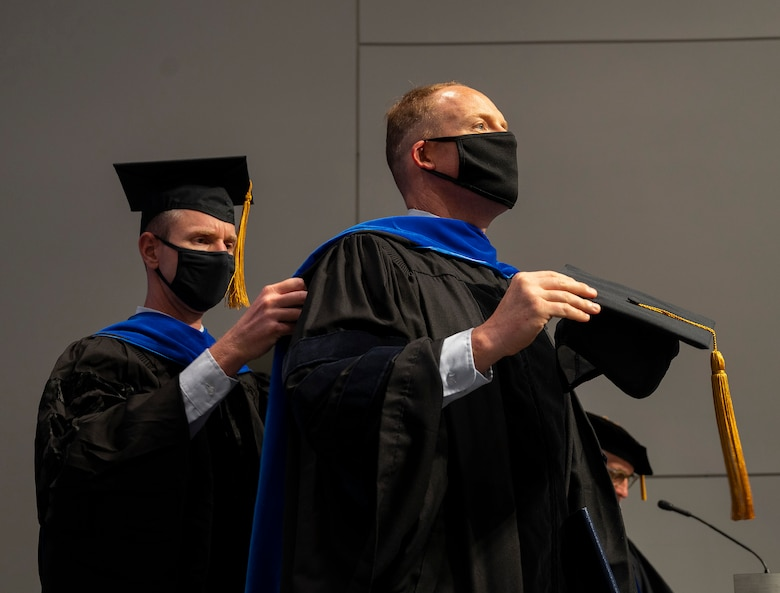 During an Air Force Institute of Technology graduation ceremony on Sept. 16, 2021, Lt. Col. James Rutledge, associate professor of aerospace engineering and senior military faculty, adjusts the hood of his student, Lt. Col. Matthew Fuqua, as Fuqua receives his Doctor of Philosophy in Aeronautical Engineering. (U.S. Air Force photo by R.J. Oriez)