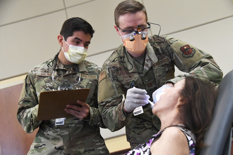 U.S. Air Force Capts. Giany Salinas and Sean Palmer, 81st Dental Squadron dental residents, provide a dental exam on Mary Patano, wife of retired Master Sgt. Nick Patano, during the 10th Annual 81st Medical Group Health Expo inside the Bay Breeze Event Center at Keesler Air Force Base, Mississippi, October 1, 2021. The 81st MDG hosted the walk-in event which included information booths and scheduling appointments for multiple types of cancer and chronic diseases in honor of Breast Cancer Awareness Month. (U.S. Air Force photo by Kemberly Groue)