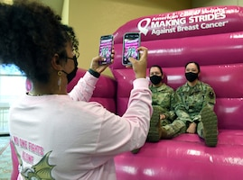 U.S. Air Force Tech. Sgt. Elaina Pea, 81st Diagnostic and Therapeutics Squadron diagnostic imaging NCO in charge, takes a photo of Chief Master Sgt. Paula Eischen, 81st Medical Group superintendent, and Col. Lynne Bussie, 81st MDG deputy commander, during the 10th Annual 81st MDG Health Expo inside the Bay Breeze Event Center at Keesler Air Force Base, Mississippi, October 1, 2021. The 81st MDG hosted the walk-in event which included information booths and scheduling appointments for multiple types of cancer and chronic diseases in honor of Breast Cancer Awareness Month. (U.S. Air Force photo by Kemberly Groue)