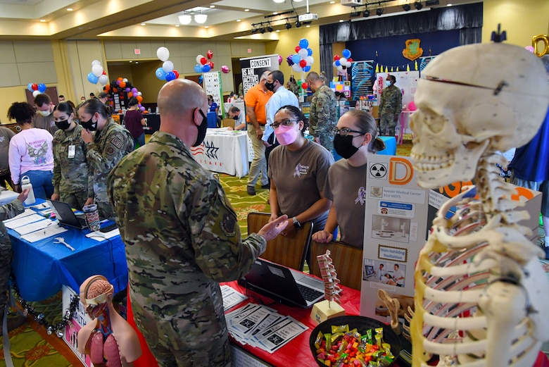 U.S. Air Force Col. William Hunter, 81st Training Wing commander, gathers radiology information from Staff Sgt. Samantha Redd, 81st Diagnostic and Therapeutics Squadron computed tomography technician, and Staff Sgt. Erica Scheerer, 81st MDTS diagnostic imaging technician, during the 10th Annual 81st Medical Group Health Expo inside the Bay Breeze Event Center at Keesler Air Force Base, Mississippi, October 1, 2021. The 81st MDG hosted the walk-in event which included information booths and scheduling appointments for multiple types of cancer and chronic diseases in honor of Breast Cancer Awareness Month. (U.S. Air Force photo by Kemberly Groue)