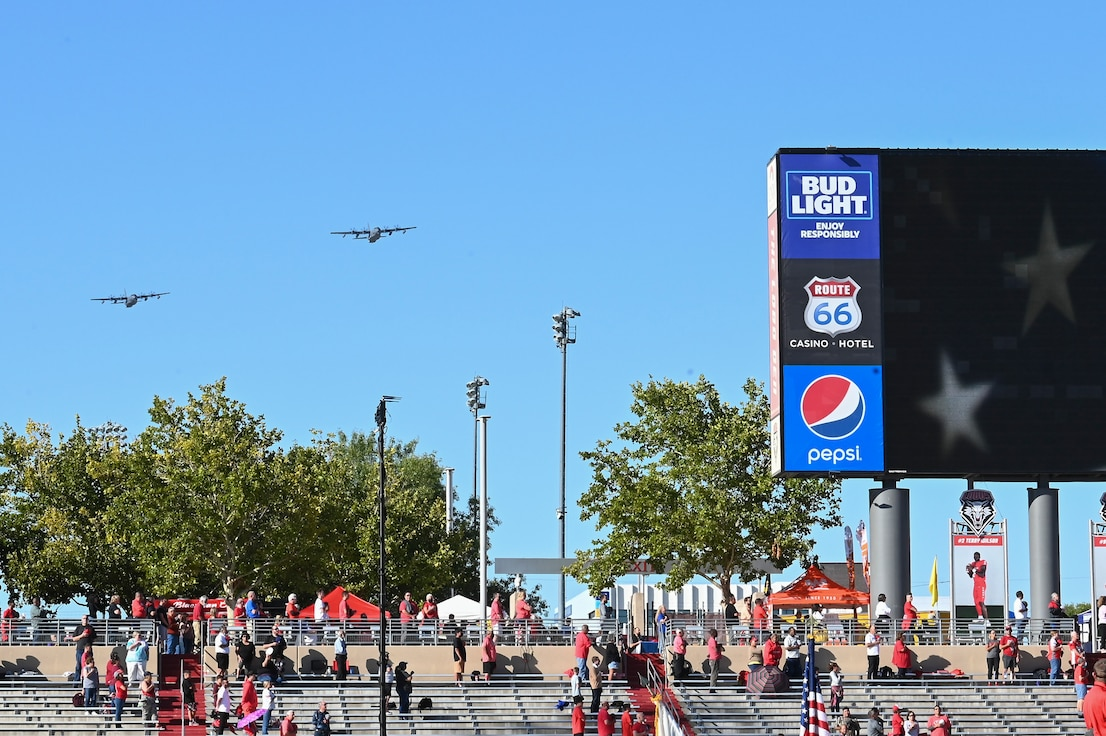 two large military aircraft flying over a college football stadium