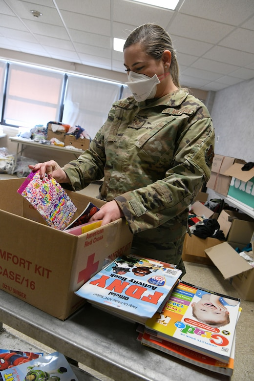 New York Air National Guard Staff Sgt. Scarlett Yates, assigned to the 106th Air Rescue Wing, sorts through donated books for Afghan children at the temporary medical isolation dormitory at Liberty Village, Joint Base McGuire-Dix-Lakehurst, New Jersey, Sept. 27, 2021. Yates helped deliver an Afghan baby at the base Sept. 7.