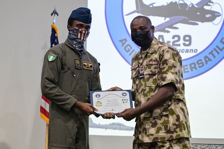 Nigerian Air Force Air Vice Marshal Sule Lawal, Nigerian A-29 program lead foreign liaison officer, right, recognizes Nigerian Air Force A-29 Super Tucano aircraft pilot, left, as a distinguished graduate for the mission qualification syllabus during the NAF A-29 pilot graduation ceremony at Moody Air Force Base, Georgia, Sept. 2, 2021. Upon graduating, the NAF pilots are qualified to strafe with two .50-caliber machine guns, shoot high explosive rockets, and drop both general purpose and laser guided bombs. (U.S. Air Force photo by Senior Airman Rebeckah Medeiros)