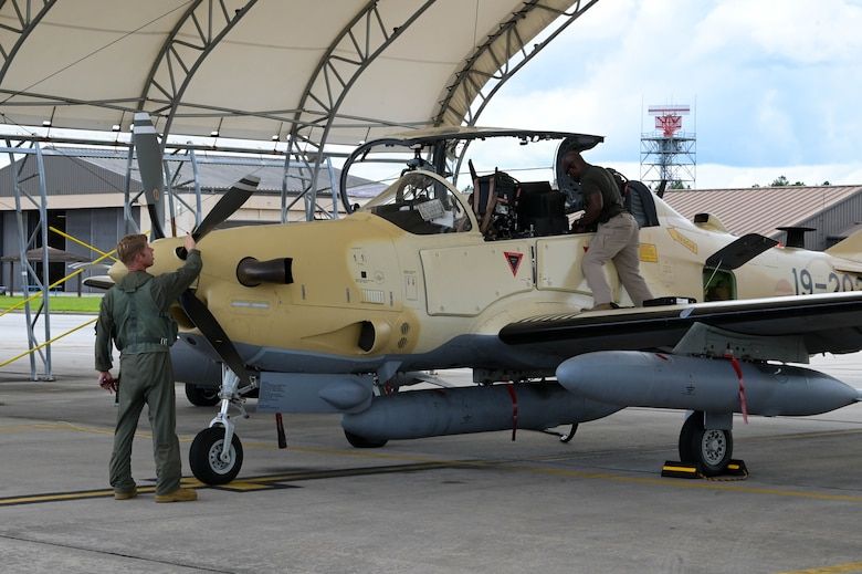 An A-29 Super Tucano aircraft pilot from the 81st Fighter Squadron, left, performs a preflight inspection at Moody Air Force Base, Georgia, Sept. 15, 2021. After more than a year of training, the final batch of aircraft are finally being sent to Nigeria. (U.S. Air Force photo by Senior Airman Rebeckah Medeiros)