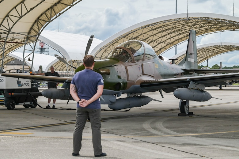 U.S. Air Force contractor Travis Smith, 81st Fighter Squadron A-29 Super Tucano aircraft technician, prepares to marshal an A-29 Super Tucano pilot for departure at Moody Air Force Base, Georgia, Sept. 15, 2021. The aircraft are being transported to Nigeria by U.S. Air Force contracted pilots. (U.S. Air Force photo by Senior Airman Rebeckah Medeiros)