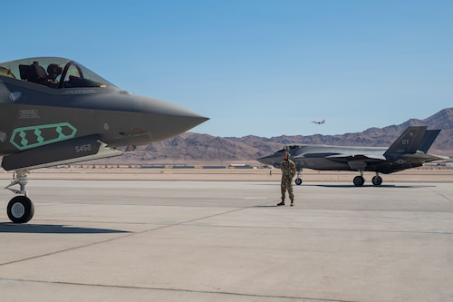Airman 1st Class Javier Farcia-Bustos waits for an F-35A pilot assigned to the 442nd Test and Evaluation Squadron to complete pre-flight checks on the flight line at Nellis Air Force Base, Nevada, Sept. 21, 2021. The 442nd and 59th Test and Evaluation Squadrons led Air Combat Command's portion of a nuclear design certification test with maintenance support from the 57th Aircraft Maintenance Squadron and Bolt Aircraft Maintenance Unit. (U.S. Air Force photo by Airman 1st Class Zachary Rufus)