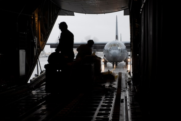 Tech. Sgt. Chad Barnette, 36th Airlift Squadron C-130J Super Hercules evaluator loadmaster, left, and Senior Airman Jerlmie Brumfield, 36th Airlift Squadron loadmaster, wait while a C-130J taxis after an incentive flight at Yokota Air Base, Japan, Oct. 1, 2021. The 36th AS used six C-130Js to showcase the flying mission during the incentive flight. (U.S. Air Force photo by Staff Sgt. Joshua Edwards)
