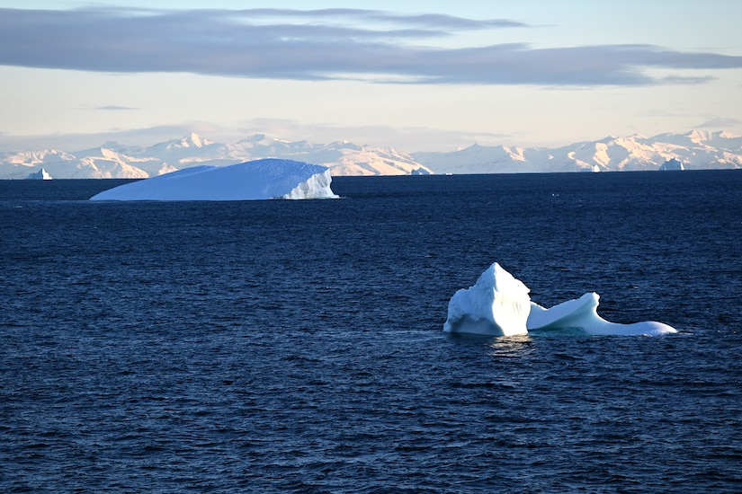 Icebergs poke out of dark blue water.