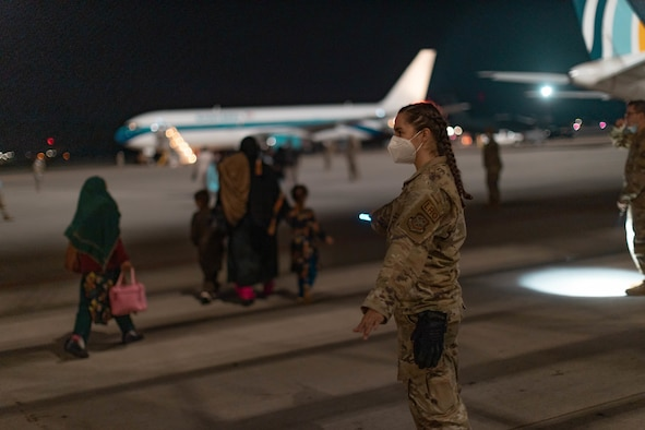 Capt. Cassandra Hill directs Afghan travelers to their awaiting aircraft at Ramstein Air Base, Germany