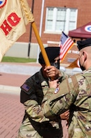 Capt. Marco G. Lara, commander, Headquarters and Headquarters Company, Special Troops Battalion, 1st Theater Sustainment Command, passes the guidon to 1st Sgt. Charles L. York, incoming first sergeant, HHC, STB, 1st TSC, during the company's change of responsibility ceremony at Fort Knox, Kentucky, Oct 1., 2021. The passing of the guidon symbolizes the transition of responsibility from one first sergeant to another.