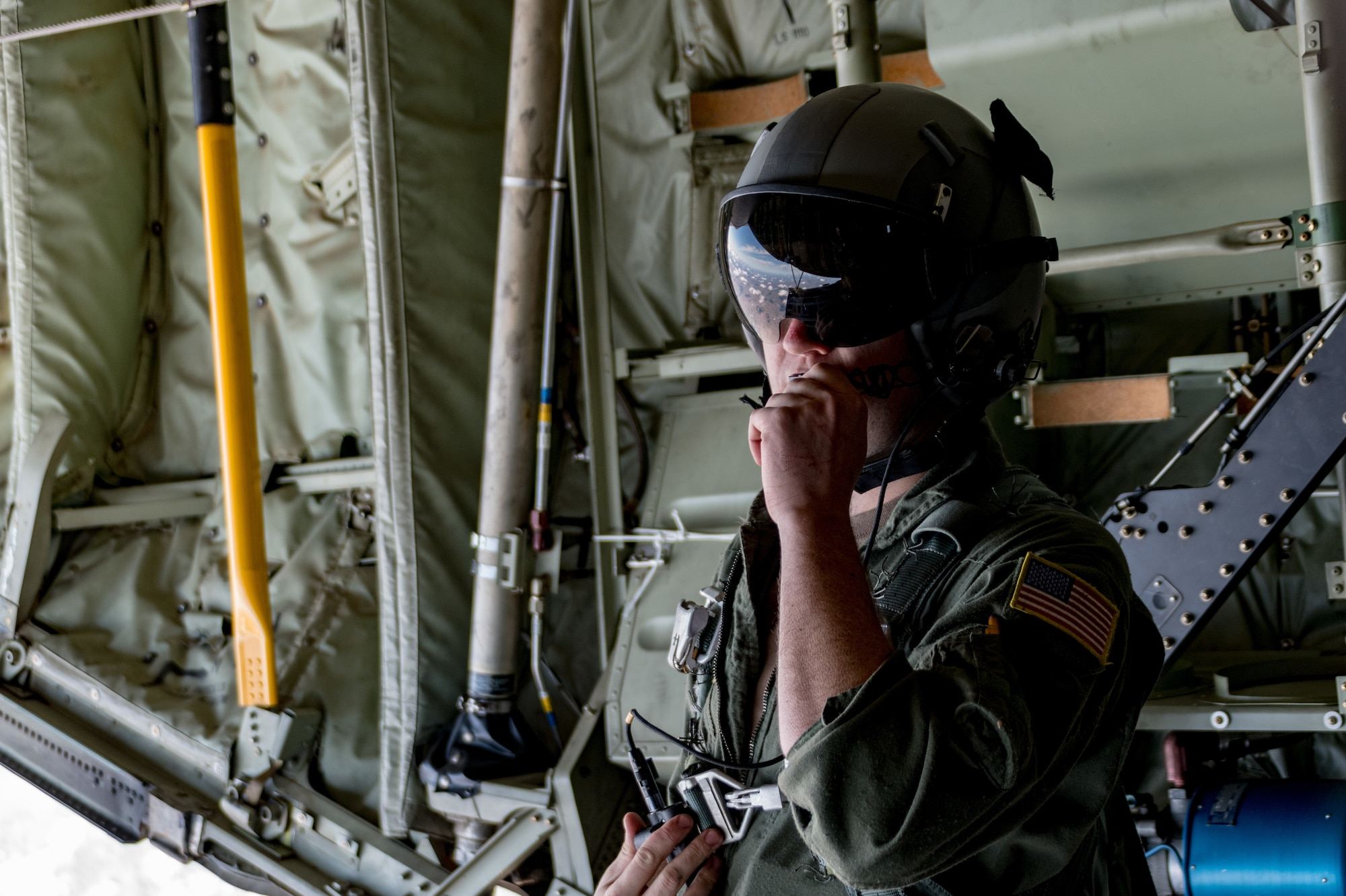 Air National Guard Senior Airman James Farless, a loadmaster from the 143d Airlift Wing, speaks into his headset, over a drop zone in Rhode Island, April 7, 2021. Aircrew from the 143 AW and U.S. Special Operations Forces partnered to perform high-altitude low-opening parachute jumps. Operating aircraft airdrop systems and supervising heavy equipment, CDS-type cargo, and paratroopers exiting the aircraft are critical functions of a loadmaster.