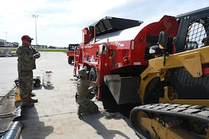 Two military members operate a large red machine as called an asphalt recycler as it heats asphalt material for use patching holes on a large concrete training runway at the North Dakota Air National Guard Regional Training Site, Fargo, N.D., Sept. 29, 2021.