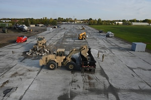 Heavy equipment and military personnel can be seen patch square holes on a concrete training runway from an elevated view at the North Dakota Air National Guard Regional Training Site, Fargo, N.D., Sept. 30, 2021.