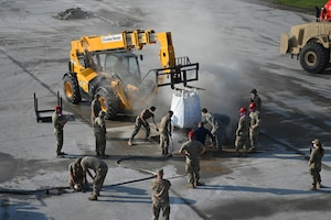 Many military members can be seen in this view from above as they rake fast-drying concrete material into place in a hole on a concrete training runway as a teleextender holds a bag in place above the hole at the North Dakota Air National Guard Regional Training Site, Fargo, N.D., Sept, 30, 2021.