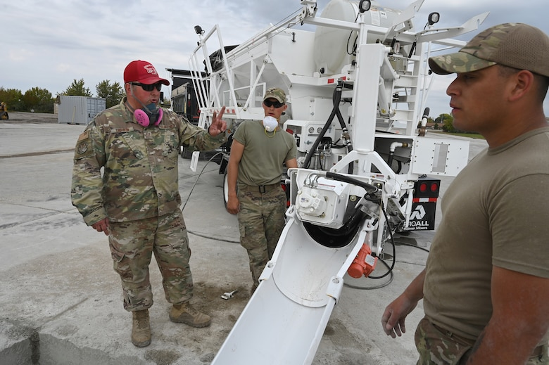 Military personnel place liquid concrete into a square hole using a machine called a volumetric mixer at the North Dakota Air National Guard Base Regional Training Site, Fargo, N.D.