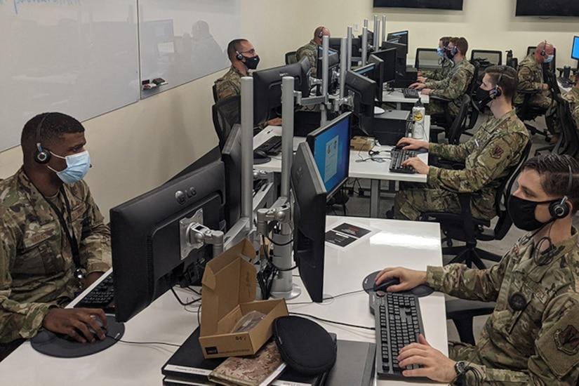 Airmen work on computers.