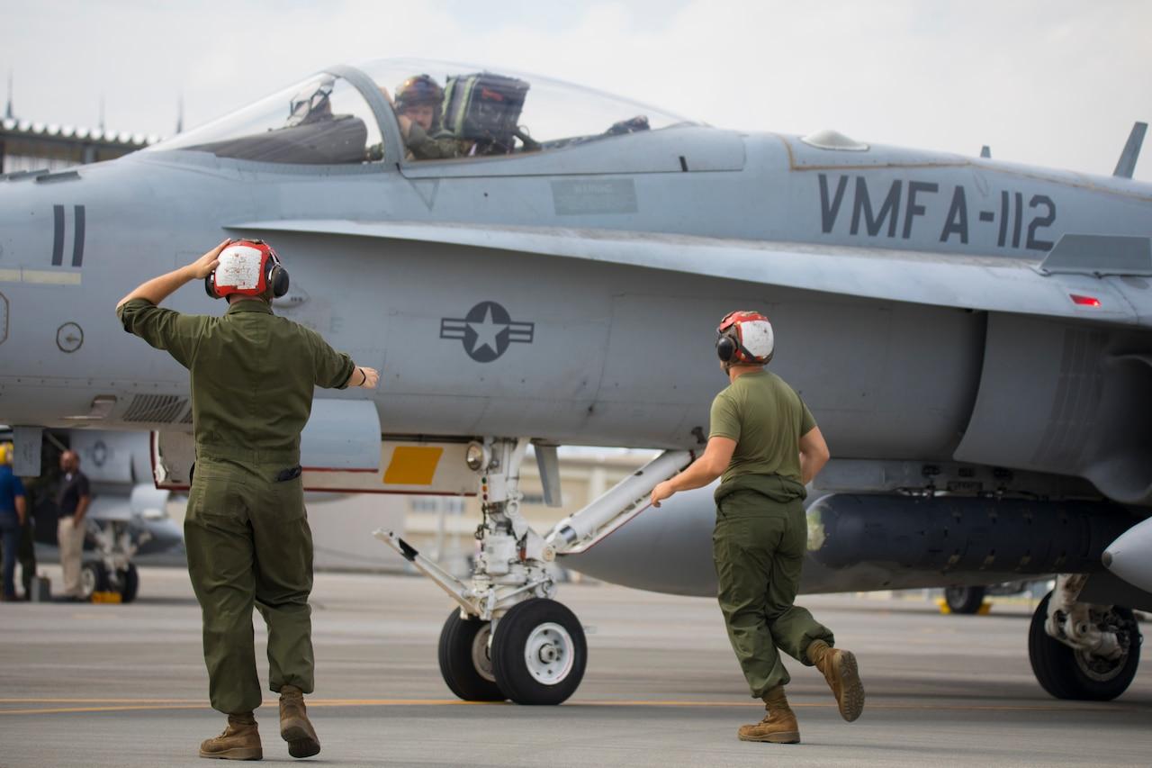 Marines work on a flight line.