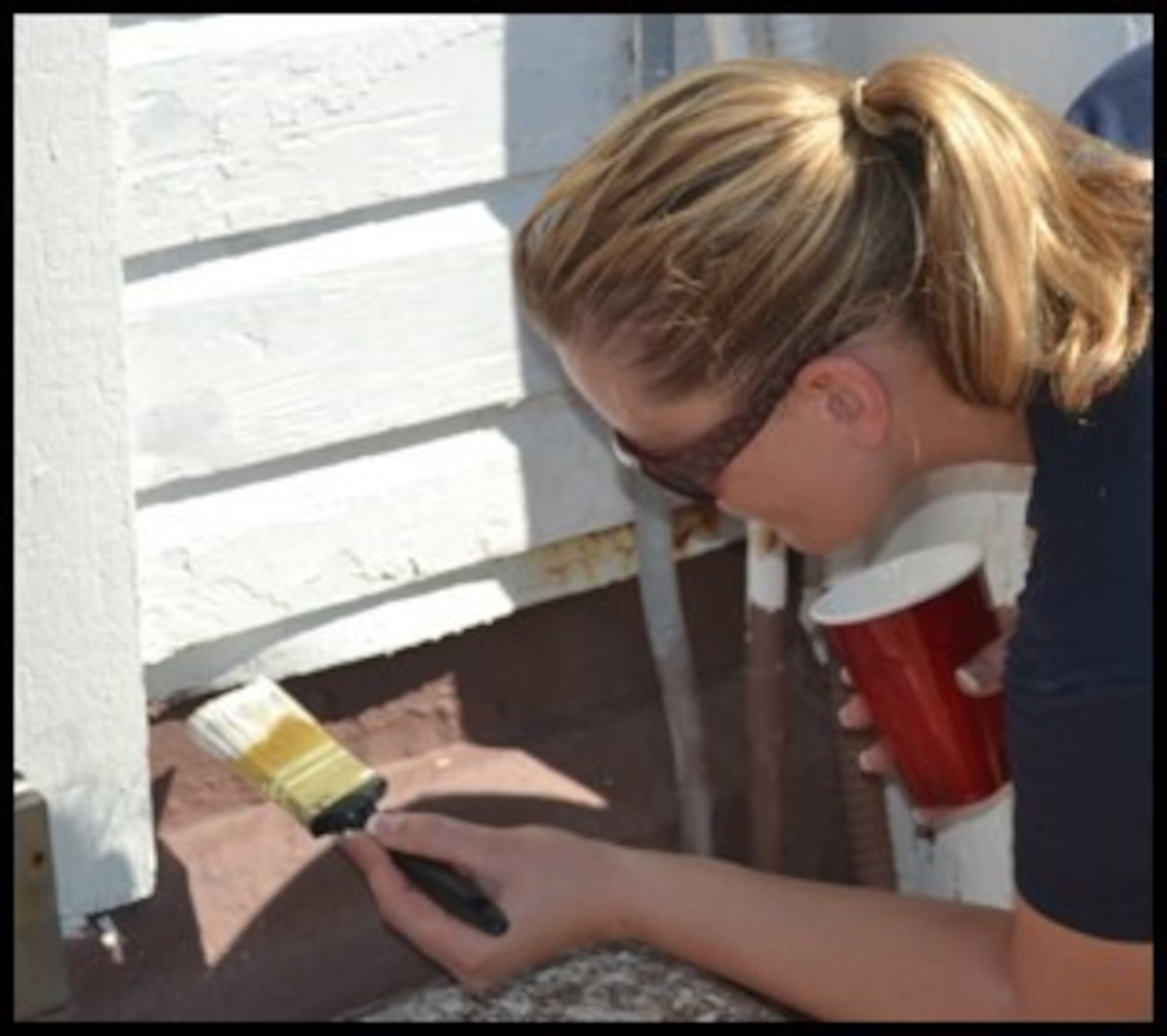 A 2012 photograph of Coast Guard Chief Petty Officer Kristin Antonides of Port Security Unit 309 painting the quarters building in her spare time. (Used with permission)