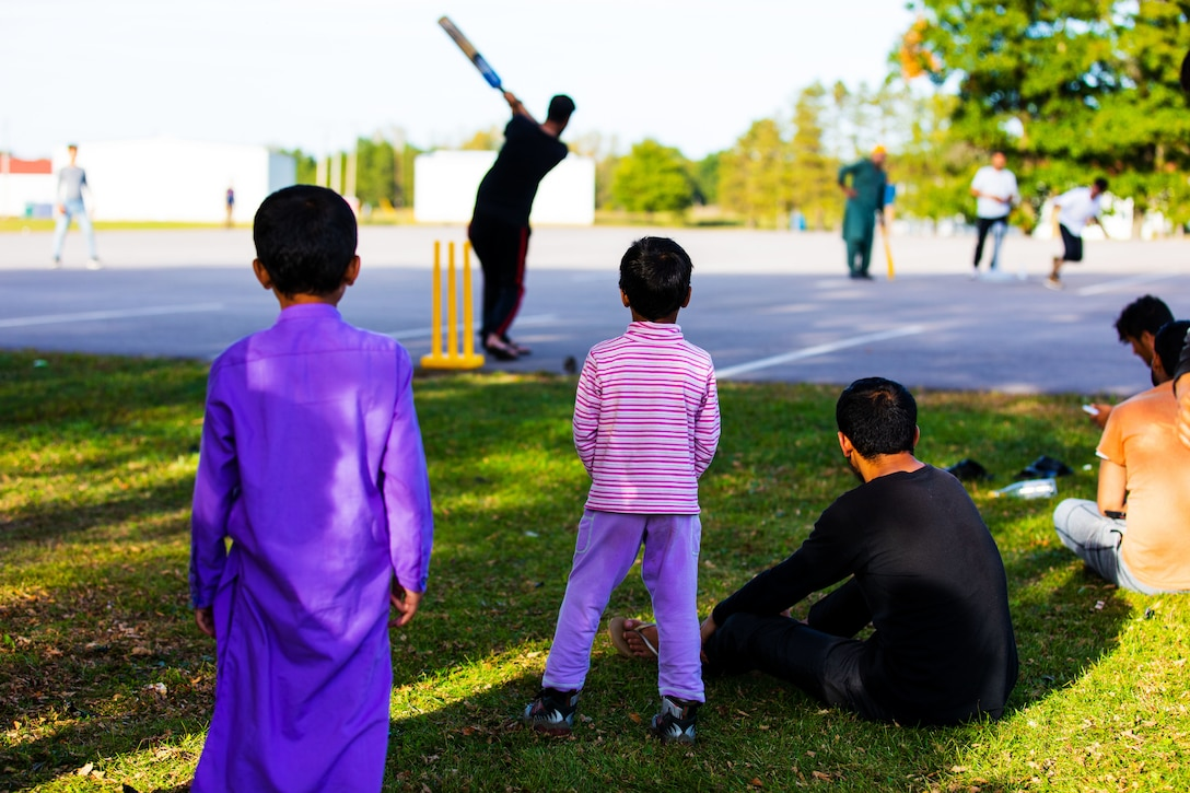 Adults and kids watch people playing cricket outside.