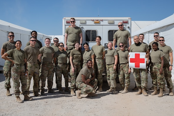 Airmen from the Task Force-Holloman triage facility medical team pose for a group photo at Aman Omid Village on Holloman Air Force Base, New Mexico, Sept. 22, 2021. The Department of Defense, through the U.S. Northern Command, and in support of the Department of State and Department of Homeland Security, is providing transportation, temporary housing, medical screening, and general support for at least 50,000 Afghan evacuees at suitable facilities, in permanent or temporary structures, as quickly as possible. This initiative provides Afghan evacuees essential support at secure locations outside Afghanistan. (U.S. Army photo by Spc. Nicholas Goodman)