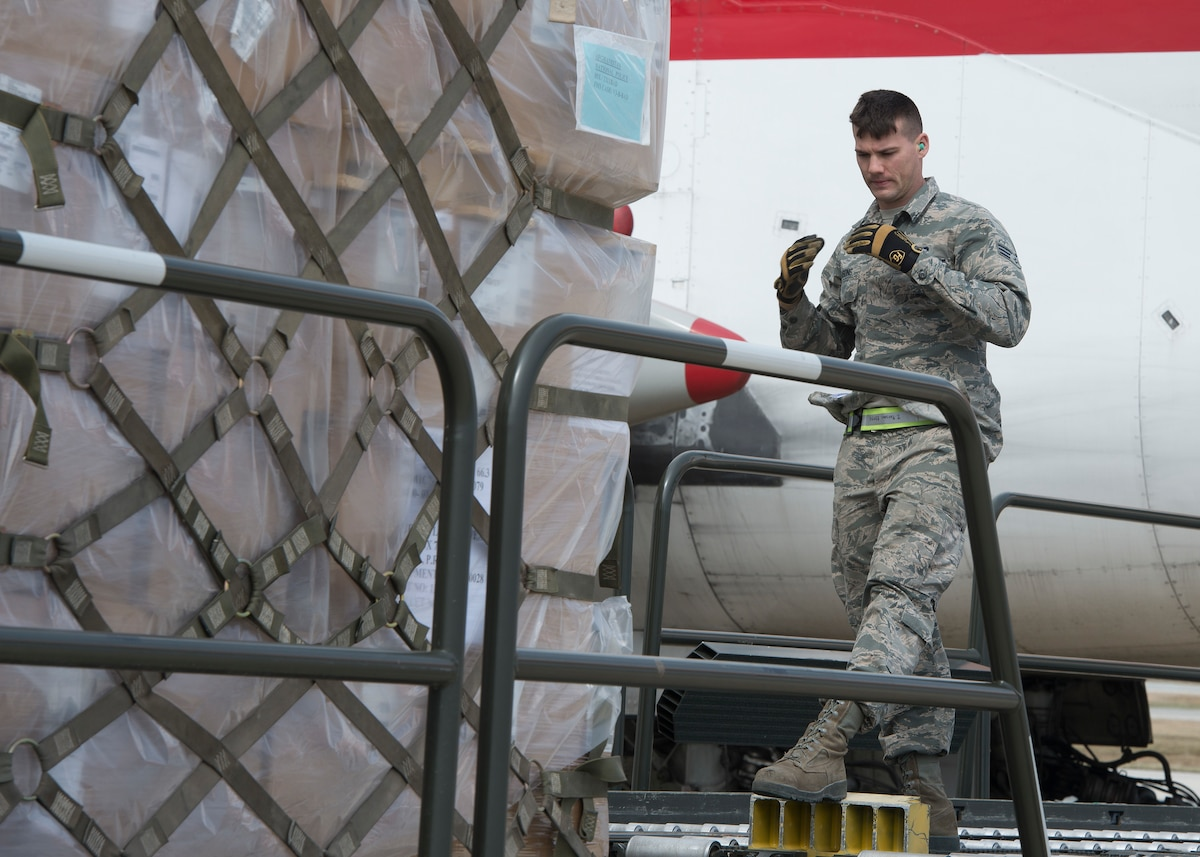 Senior Airman Zachary Parsons, 436th Aerial Port Squadron ramp services, martials a K-Loader during a cargo upload March 24, 2017, at Dover Air Force Base, Del. The 436th APS is the largest aerial port in the Department of Defense, supporting channel, contingency and exercise missions. (U.S. Air Force photo by Senior Airman Zachary Cacicia)