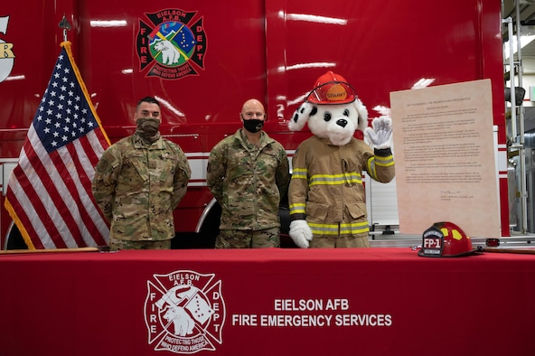 From left to right, U.S. Air Force Master Sgt. Christopher Brown, the 354th Civil Engineering Squadron deputy fire chief, Col. David Berkland, the 354th Fighter Wing commander, and Sparky the fire dog pose for a group photo during the fire prevention week proclamation signing on Eielson Air Force Base, Alaska, Sept. 17, 2021.