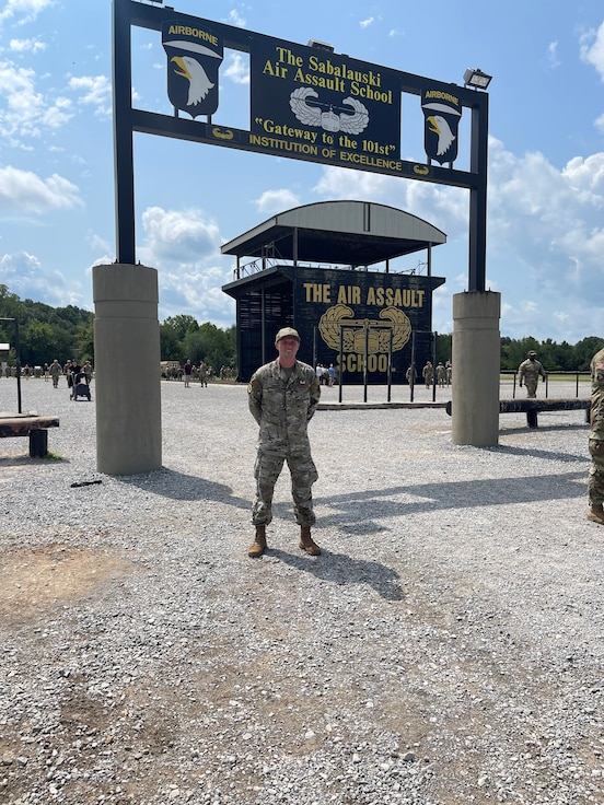 A photo of an Airman standing in front of the Army Air Assault School sign