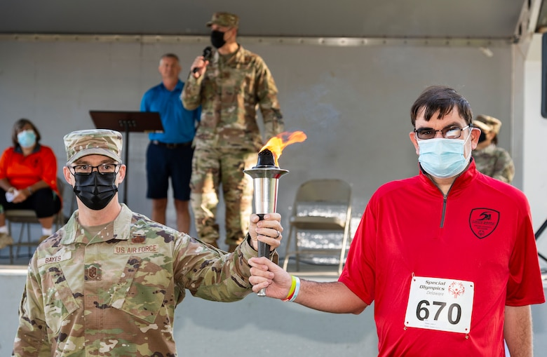 Chief Master Sgt. Timothy Bayes, left, 436th Airlift Wing command chief, delivered the Special Olympics Flame of Hope to Justin Daisey, of the Sussex Riptide as Col. Matt Husemann, 436th AW commander, officially opened the 2021 Special Olympics Delaware Cycling Classic at Dover Air Force Base, Delaware, Oct. 2, 2021. Team Dover senior leadership presented medals to the top three finishers in each event. (U.S. Air Force photo by Roland Balik)