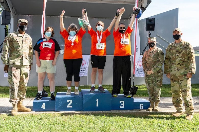 Col. Phelemon Williams, left, 436th Mission Support Group commander; Lt. Col. Kady Griffin, second from right, 436th Force Support Squadron commander and Col. Shanon Anderson, right, 436th Airlift Wing vice commander, stand with cyclists during the 2021 Special Olympics Delaware Cycling Classic at Dover Air Force Base, Delaware, Oct. 2, 2021.Team Dover senior leadership presented medals to the top three finishers in each event. (U.S. Air Force photo by Roland Balik)