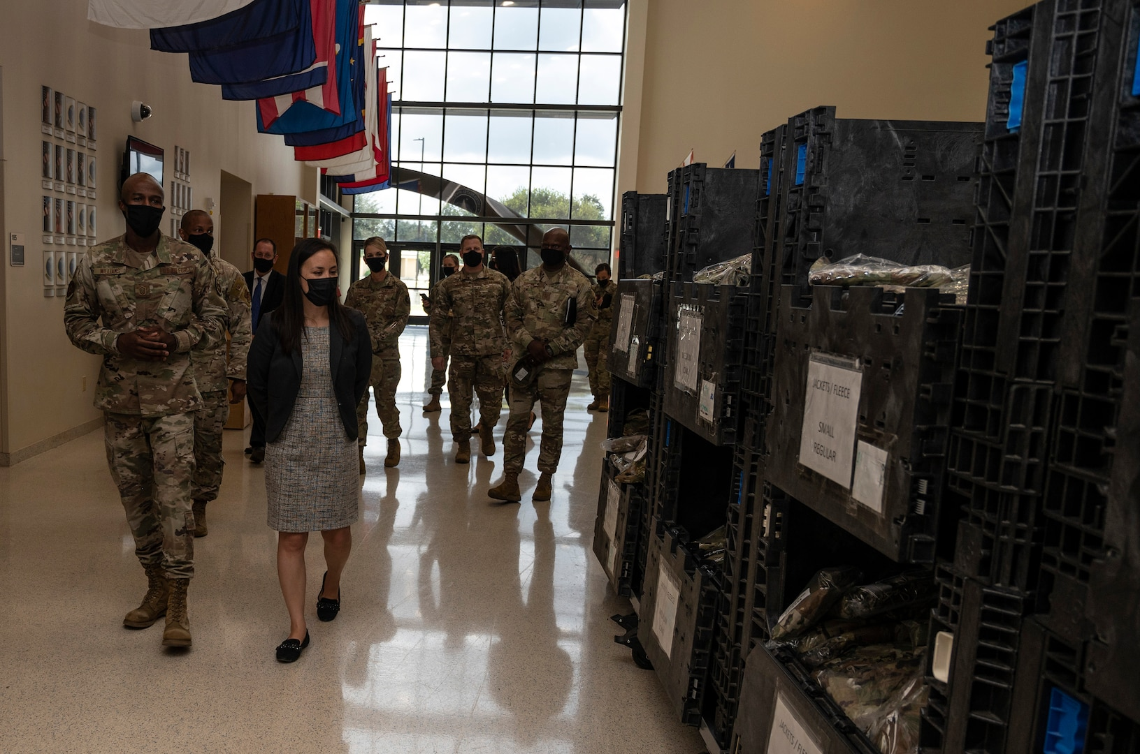 Undersecretary of the Air Force walking past BMT gear issued to trainees.