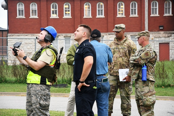 """A Civil Air Patrol drone pilot captures aerial views of """"damaged"""" buildings while other team members evaluate potential structural instability during an earthquake exercise involving the Missouri Air National Guard and state and local partners in St. Louis Oct. 2, 2021."""