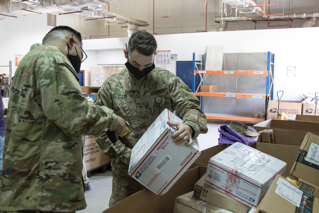 Spc. Matthew A. Hernandez, a Soldier assigned to 678th Human Resources Company, scans a package held by Cpl. Brett D. Ellis, a human resources specialist assigned to the Fort Bragg, North Carolina, based Headquarters and Headquarters Company, 3rd Expeditionary Sustainment Command, at the post office on Camp Arifjan, Kuwait, on Oct. 2, 2021. Ellis, a native of Fort Worth, Texas, is one of many Soldiers deployed to Kuwait staffing the 1st Theater Sustainment Command Operational Command Post.