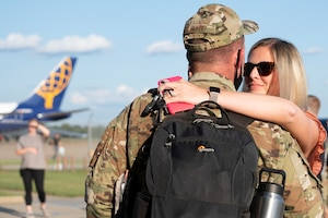 A man in uniform and woman hug.