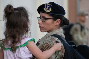 A mother in uniform holds her daughter.